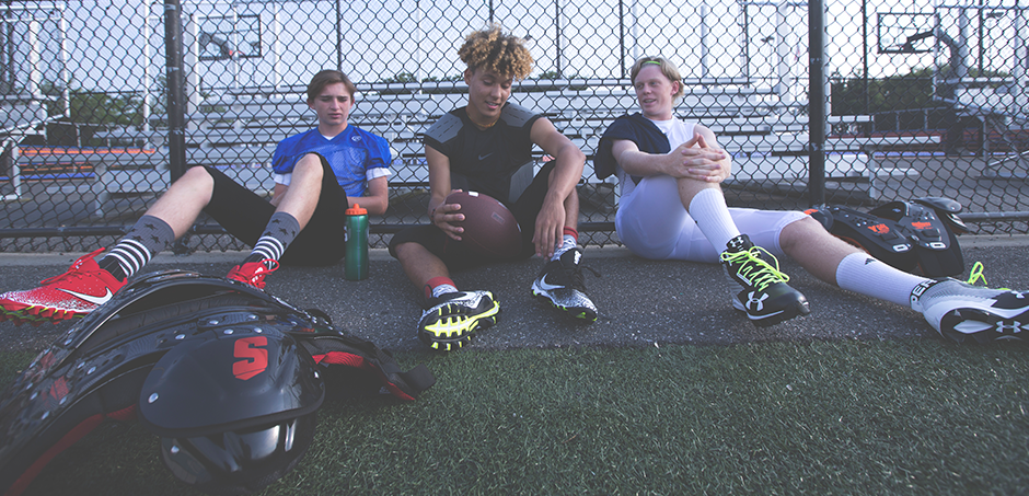 three boys hanging out at football practice in cleats and gear
