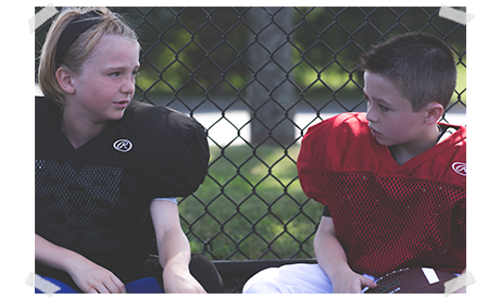 two kids talking to each other on the bench at football practice