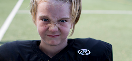 young boy at football practice in black jersey and pads