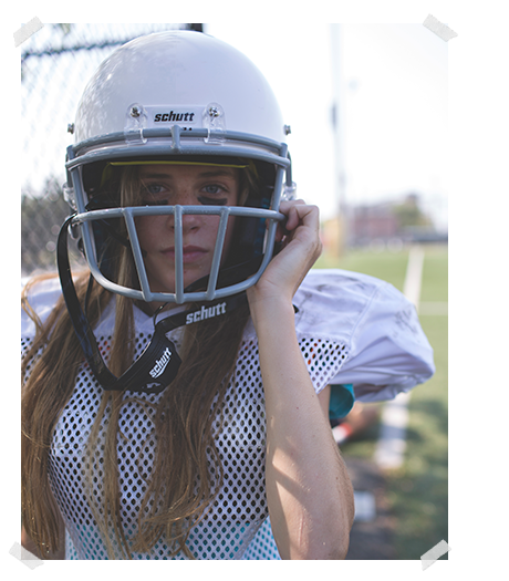 girl in white football jersey adjusts the straps on her white football helmet