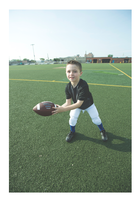 boy in black shirt and white football pants catches a pass