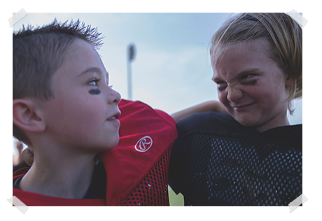 boy in red football jersey with arm around boy in black football jersey