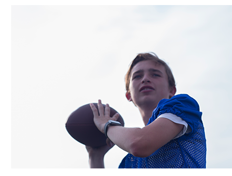 boy in blue mesh shirt gets ready to throw a football