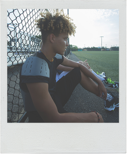 boy sitting at football practice looking at the field in black football pants and black nike cleats