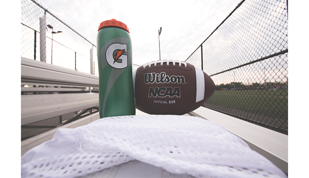 football leaning on a green gatorade bottle
