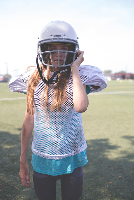 girl in white football jersey and blue undershirt adjusts the straps on her white football helmet