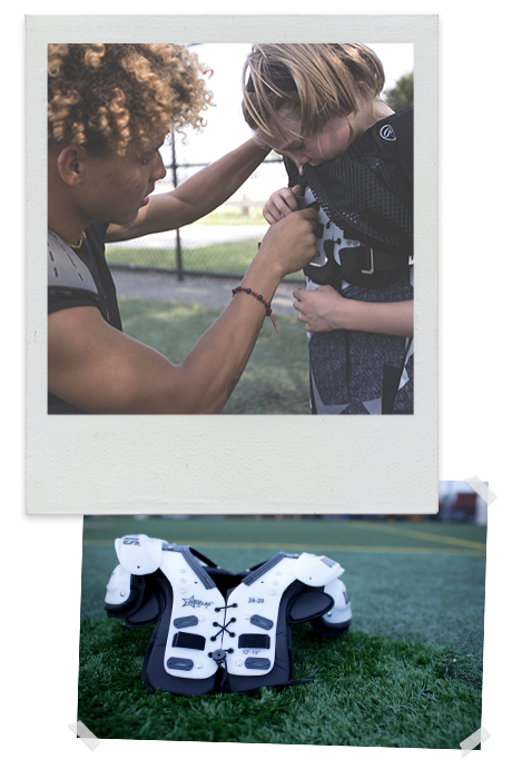 older boy helps younger boy with his straps on his football shoulder pads