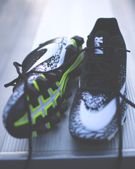 black white and green football cleats sitting on the bleachers