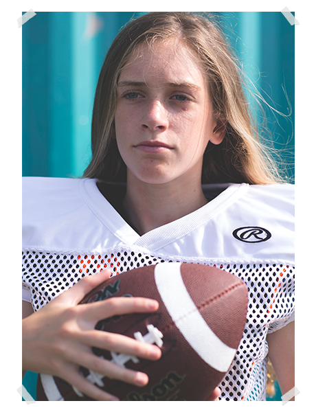 girl in white football jersey with shoulder pads on holds Wilson football