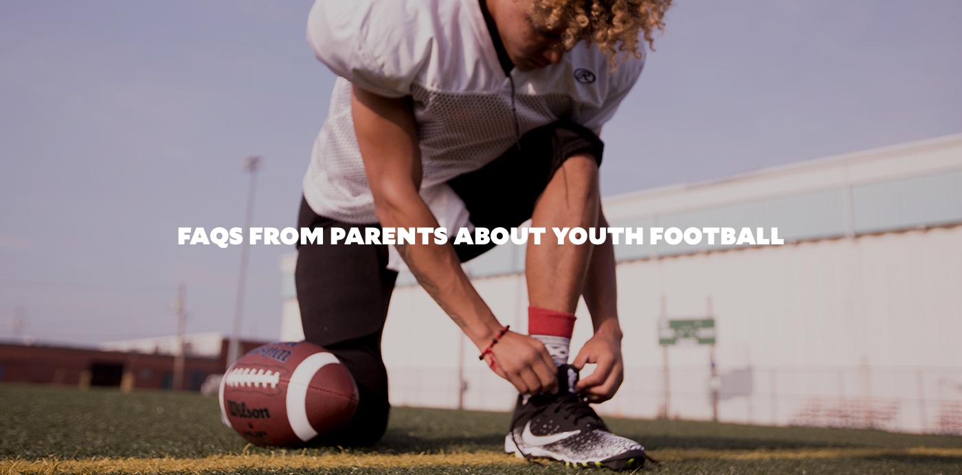 boy in white football jersey and black football pants bending over to tie black nike football cleats